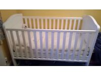 White cot bed with height adjustable base.