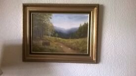 Framed picture of a forest and hills.