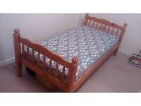 Pine single bed with slatted base and mattress.