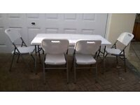 folding white table and four folding chairs