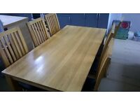 solid oak table and six chairs with black faux leather seats