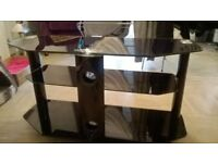 "black glass tv stand with 3 shelves. fits into corners and holds a 42"" flat screen tv."