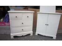 Cream painted bedside tables with drawers and cupboards.