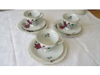 Three vintage china teacups with saucers and side plates.