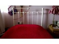 Cream metal single bed frame and mattress.