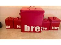 red bread bin with biscuit sugar coffee amd tea tins