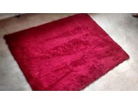 RUBY RED FINE SHAGGY RUG MEASURES APPROX 124 CM X 160 CM.