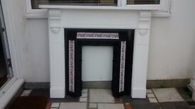 Victorian (?) fireplace surround: wooden casing (painted white), cast iron with pink floral tiles.
