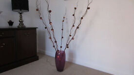 purple glass vase with branches that light up