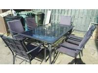 6 seater outdoor glass top table with padded seat cushions