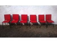 6 red and black stacking office chairs.