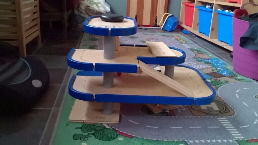 Toy wooden garage with ramps and lift.
