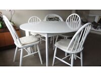 Dining table and 4 chairs. Circular table with an insertion panel to make it into an oblong table.