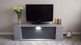 Beautiful solid TV cabinet, brand new, didn't match decor. Grey colour with darker glass doors.