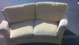 curved two seater sofa in cream in good condition bargain at £75 can deliver