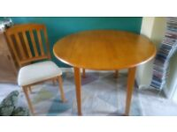 Dining table (two drop leaves) and four matching fabric chairs - solid medium toned wood.