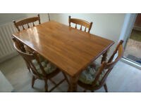 Farmhouse style kitchen table with 4 cushioned chairs.