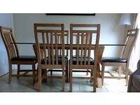 Solid oak 6 seater dining table with glass top and 6 solid oak chairs with brown leather seat