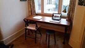 A vintage industrial oak desk with tubular steel legs.