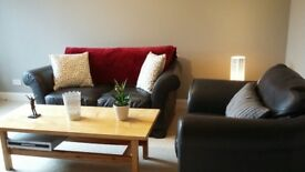 Two seater sofa and armchair for sale. Grey leather