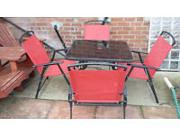 metal framed black glass garden table and 4 red folding chairs