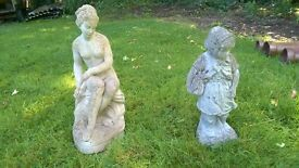 Two stone statues, one lady,one girl,old and weathered.