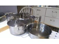 large and small stainless steel pans with lids, frying pan