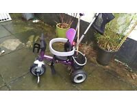 Kids purple trike with sun shade. Also comes with a cup holder and basket