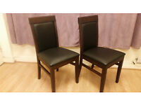 Two Dark wood and black leather dining chairs