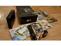 Black nintendo wii with games and controllers