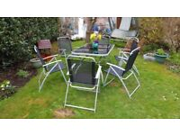 Garden table and chairs. Glass topped outdoor picnic table and 6 folding chairs..