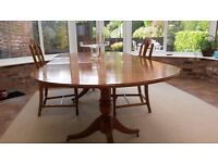 Yew veneered polished dining table with solid base and 6 chairs. Bissett & Brunton of Brighton