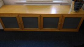 Low brown wooden cupboard with frosted glass windows