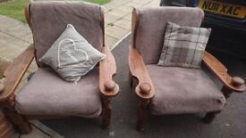 Two indoor/outdoor solid wood chairs with cushions.