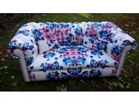 White leather two seater sofa with floral print