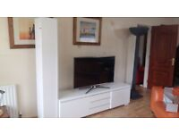 White high gloss tv units/ sideboard and matching tall cupboard.
