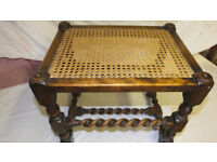 A very old (antique) stool/table with a very attractive wooden frame with open weave rattan top.
