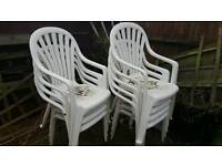9 White plastic garden chairs