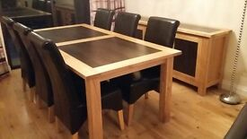 Beautiful large solid oak dining table, with 6 chocolate brown leather chairs. Excellent condition.