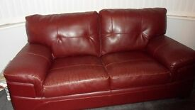 2 x 2 seater red leather sofas and matching footstool with storage