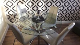 Next Round glass dining table and 6 chairs.