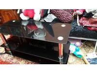 Black thick glass tv table hold up to 70kg excellent condition .