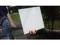 33 white ceramic tiles, 250mm x 250mm square.