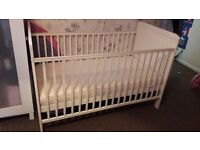 White cot bed with teething rails and mattress