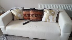 Good condition two seater Ikea couch with three brand new couch covers