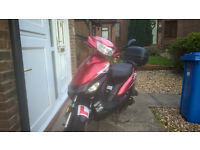 Red and black 50 cc moped with security chain and top box