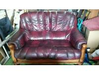 2 x dark red leather sofas and footstool. Solid wood frames