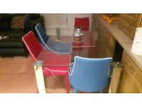 Glass dinning room table and 4 coloured chairs