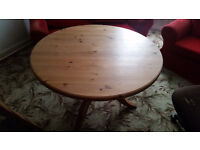 An unpolished 110cm diameter circular wooden dining table on solid tripod legs