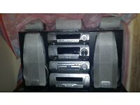 Silver coloured kenwood stereo system with remote, cd player, radio, x2 cassette, x2 speaker, woofer